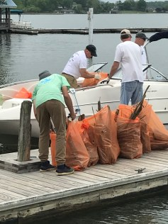 Volunteers at Crazy Horse Marina unload from a boat debris collected on the water May 5 as part of Take Pride in Smith Mountain Lake. The event's signature orange bags, along with work gloves and a T-shirt, are available for free to all registered volunteers, including homeowners who clean up around their own shoreline. Download a signup form at takepridesml.com.