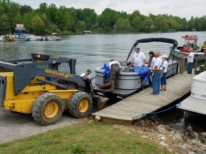A skid steer loader operated by Take Pride in SML committee member Joe Long pulls up to be loaded with debris collected by members of Smith Mountain Striper Club and Smith Mountain Lake Marine Fire/Rescue on May 5. More than a dozen volunteers took part in the cleanup event at Westlake Waterfront at Indian Point Marina.